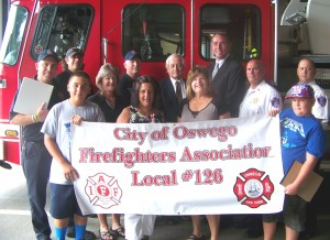 Oswego Mayor Tom Gillen joins members of the City of Oswego Firefighters Association Local 126 in presenting a donation of school supplies to the United Way?s Stuff-A-Bus campaign