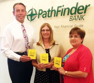 Patrick Dewine joins Pathfinder Bank employees Melissa Miller (c) and Carol Shannon (r) in displaying United Way?s Paper Buses