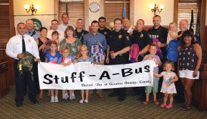 The City of Oswego along with Oswego Police and Fire Departments are once again supporting the United Way of Greater Oswego County?s Stuff-A-Bus Campaign. The annual school supply drive works to ensure that every child in Oswego County has the tools they need to be ready to learn on the first day of school. Above, United Way Executive Director Patrick Dewine, Stuff-A-Bus Co-Chair Person Laurie Kelly, Oswego Mayor Billy Barlow, Fire Chief Randy Griffin with members of the Oswego Fire Department, and Police Chief Tory DeCaire with members of the Oswego Police Department are pictured with a group of community supporters before the 2018 Stuff-A-Bus Campaign, which collected more than 46,000 school supply items for local children in need. For more information, call the United Way at 315-593-1900.